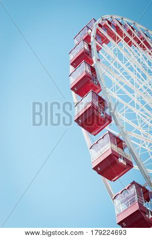 Bright red Ferris wheel compartments against a blue sky.