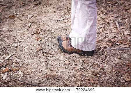 A woman wearing hiking boots and khaki pants standing on a trail with brown leaves.