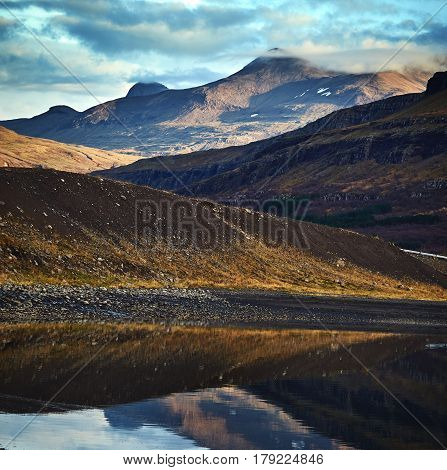 Beautiful view of the Iceland fjord. A trip to Iceland in the fall. water and reflections in the foreground, in the background the mountains and sky. Reflection of mountains in the lake