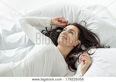 Attractive Woman In White Sleepwear Awakening In Bed At Home