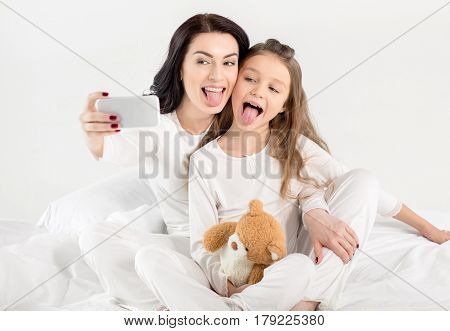 Happy Mother And Daughter In Pajamas Taking Selfie With Smartphone On Bed
