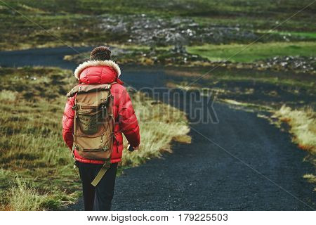 man travel on a road in the mountains in Iceland. A man walking along a rural road through lava fields in Iceland
