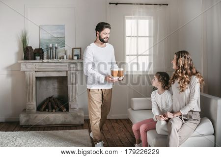 Smiling Father Bringing Coffee In Paper Cups For Mother And Daughter At Home