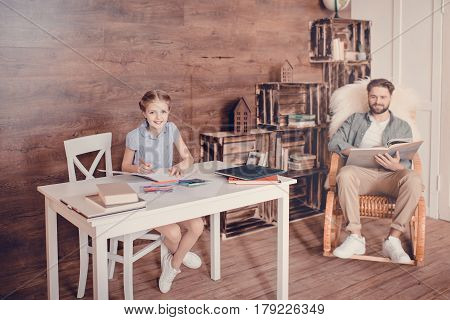 Little Girl Doing Homework And Sitting At Table, Father With Book Sitting Behind