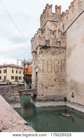 Tourists Stand On Bridge Leading To Scaligero Fortress In Sirmione