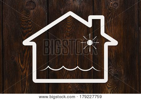 Paper house with water waves inside deluge or flooding abstract conceptual image on wooden background