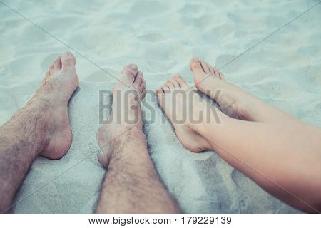 Woman and man legs foot in the beach. Feet sand
