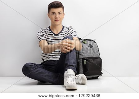 Teenager sitting on the floor next to a backpack and leaning against a white wall