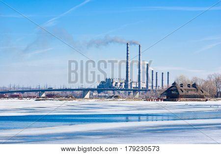 Electric power station beside a river - winter industrial landscape in Ukraine.