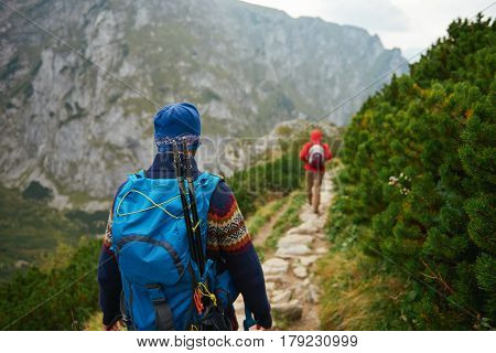 Rearview of two young men in hiking gear wearing backpacks walking together along a rocky trail high up in a rugged mountain range