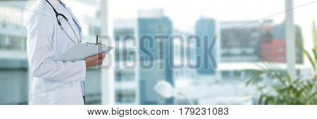 Female doctor holding clipboard and looking away against laptop on desk by glass window in office