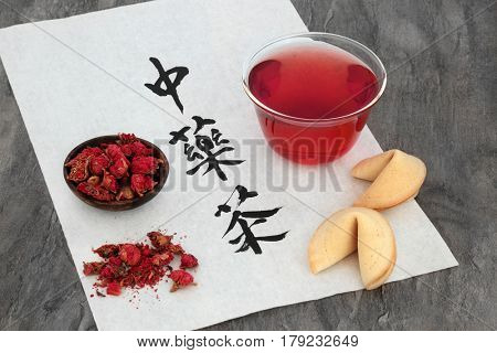 Pomegranate flower tea in a glass cup with fortune cookies on rice paper with calligraphy script.  Translation reads as chinese herb tea.
