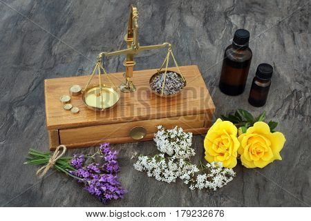 Valerian, lavender and rose flowers used in natural alternative medicine with old brass scales and essential oil bottles.