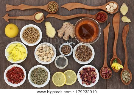 Oriental herb tea selection in china bowls and wooden spoons with glass tea cup and strainer over oak background. Used also in chinese herbal medicine,
