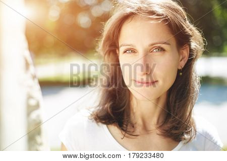 Beautiful girl in the park, Smiling and looking forward . Weekend and rest in the park