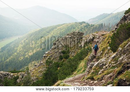 Rearview of a young man wearing hiking gear and carrying a backpack walking alone along a rocky trail high up in the mountains