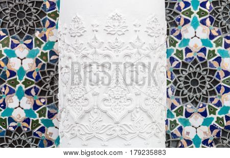 Bas-reliefs with patterns and ornaments on a wall background with mosaic