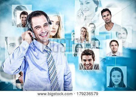 Smiling businessman using headset against blue background