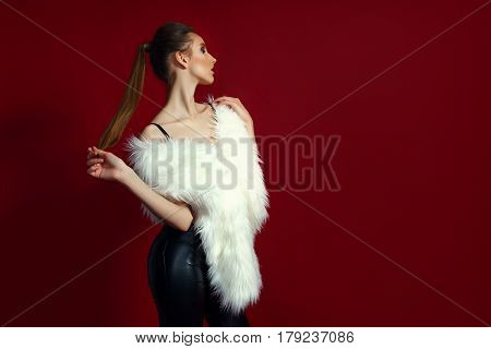 Portrait of glam girl in white fur on red background. Fashion photo