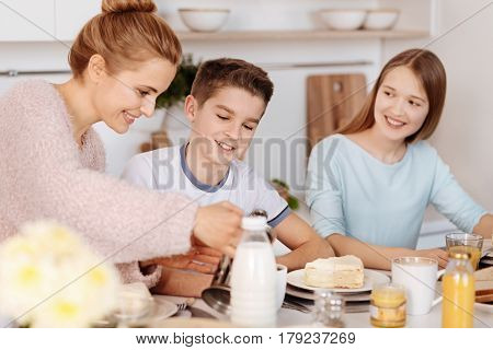Substantial meal. Cheerful caring mother pouring tea and having breakfast with her children while sitting in the kitchen