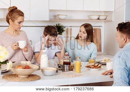 Dont feel depressed. Moody cheerless boy sitting at the table and his sister supporting him while having meal with their parents