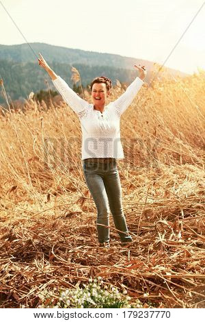 Woman enjoying mid-fifties the first rays of the Sun in a belt of reeds in the spring.