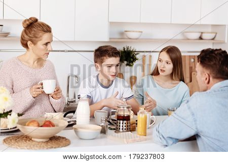 Lively conversation. Emotional boy having pleasant conversation with his family while sitting at the table and having breakfast