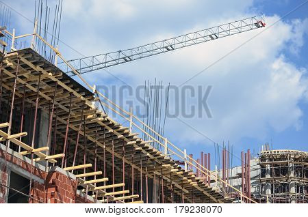 Detail of a reinforced building under construction and a crane