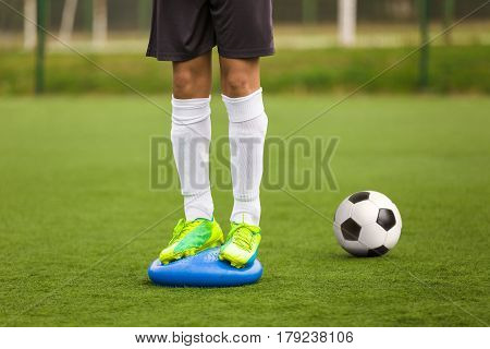 Sports Balance Training. Stability Soccer Training on Balance Cushion. Soccer Skills Training Session. Players Training on the Field. Grass Football Field. Coaching Soccer Equipment for Field Training