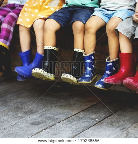 Diversity Group Of Kids Sit Together Rubber Boots