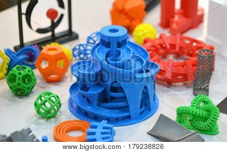 Models printed by 3d printer. Bright colorful objects printed on a 3d printer on a table