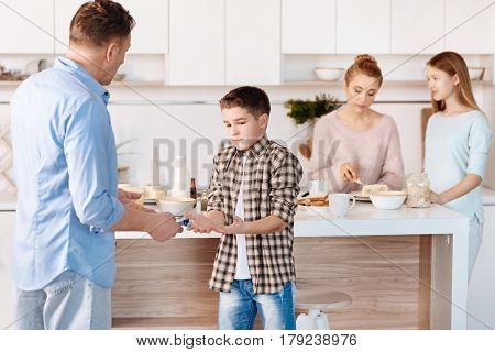 Its not mine. Serious man holding cigaretts and punishing his son for smokign while standign in the kitchen poster