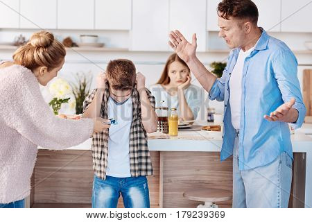It is prohibited. Furious family couple holdign cigaretts and punishing their son while standing in the kitchen