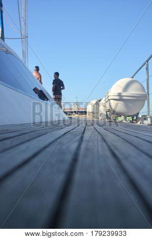 Wooden floor on big yacht. Two men on bakcground