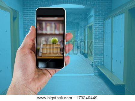 Digital composite of Hand with phone showing book pile with green apple against hallway with blue overlay