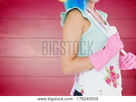 Digital composite of Woman in apron with duster against blurry pink wood panel