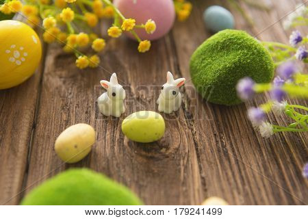 Rabbits with easter eggs on wooden table. Cute Little easter bunny. Happy Easter.