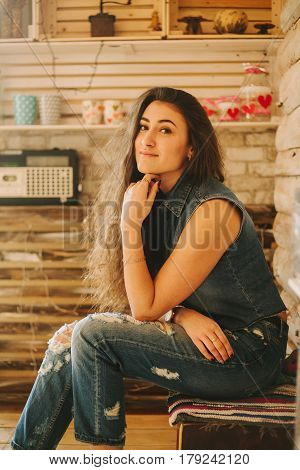 curly hipster girl in tattered jeans on a wooden background