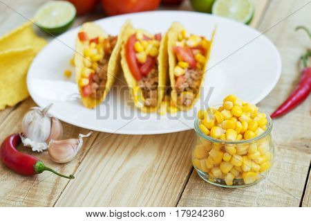 Ingredients for mexican tacos: yellow corn chili pepper garlic crispy taco shells lime and tomatoes