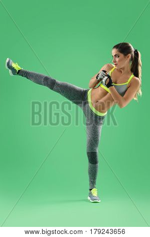 Kickboxing woman. Vertical shot of a female fighter in sportswear performing high kick on green background fitness sports athletics kicking kickboxing fighting fitness strength motivation concept