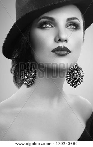 Classic beauty. Monochrome vertical studio shot of a beautiful young woman wearing a hat and professional makeup looking away black and white retro vintage classic sensuality fashion diva concept