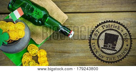 Composite image of St Patrick Day symbol against st patricks day shamrock with flag and beer bottle by pot filled with chocolate gold coins