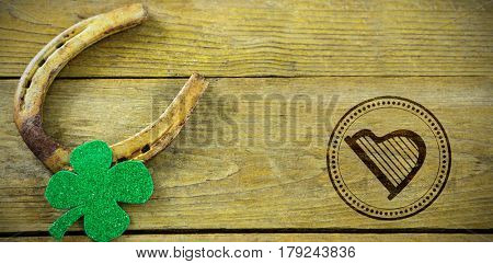 Composite image of St Patrick Day with harp symbol against st patricks day shamrock with horseshoe
