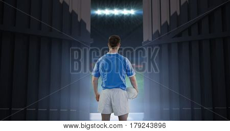 Rugby player holding a rugby ball against football pitch with flags and lights 3d