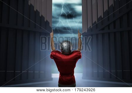 Rear view of American football player with arms raised against football pitch under stormy sky 3d