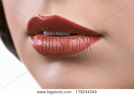 Warm colors. Close up shot of woman lips covered with dark orange glossy lipstick makeup cosmetics flawless unblemished perfect skin face care mouth features elegance beauty sexuality feminine concept