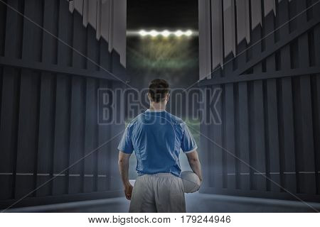 Rugby player holding a rugby ball against football pitch under bright spotlights 3d