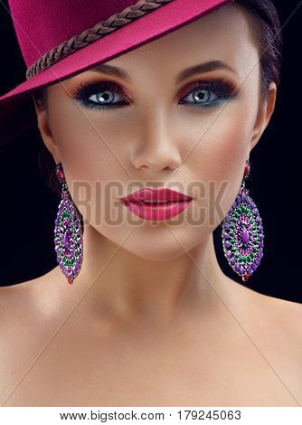 Magnificent beauty. Vertical studio close up of a gorgeous woman wearing pink hat pink lipstick and multicolored eye shadow posing on black background professional makeup fashion fabulous artistic