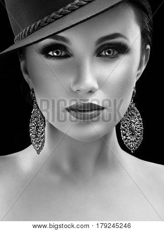 Classy woman. Vertical monochrome close up shot of a beautiful classy woman wearing professional makeup and a hat looking to the camera confidently retro vintage style perfect skin salon fashionable
