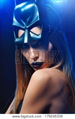 Hero or villain Vertical studio close up of a gorgeous young woman wearing black lipstick and batman mask posing in artistic blue lighting looking fiercely to the camera fashion style cosplay makeup.